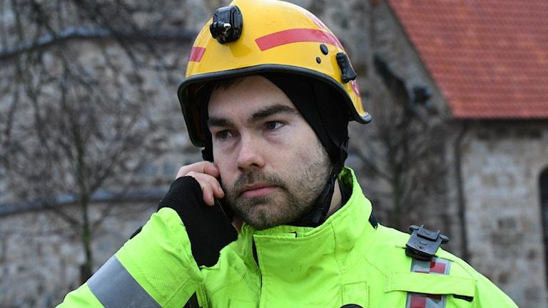 Joakim Ilmrud, räddningstjänstens informationsbefäl, tar i telefon på brandplats.