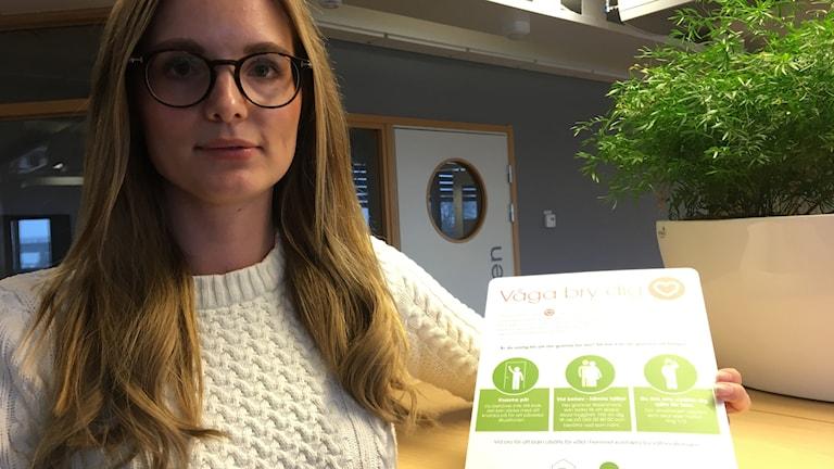 Louise Liedholm visar upp informationen som nu sätts upp i trapphusen i Helsingborgshems fastigheter.
