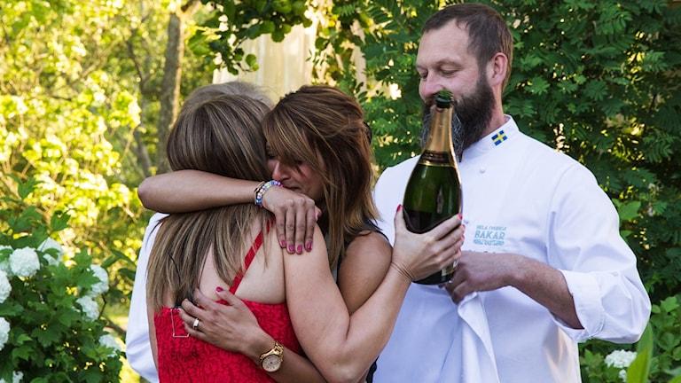 Shireen Selfelt kramas om av programeldaren Tilde och domaren Johan som håller en flaska champagne i handen.