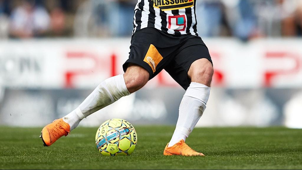 Fotbollsspelares underdel i Landskronas svartvita mundering och en skrikgul boll.
