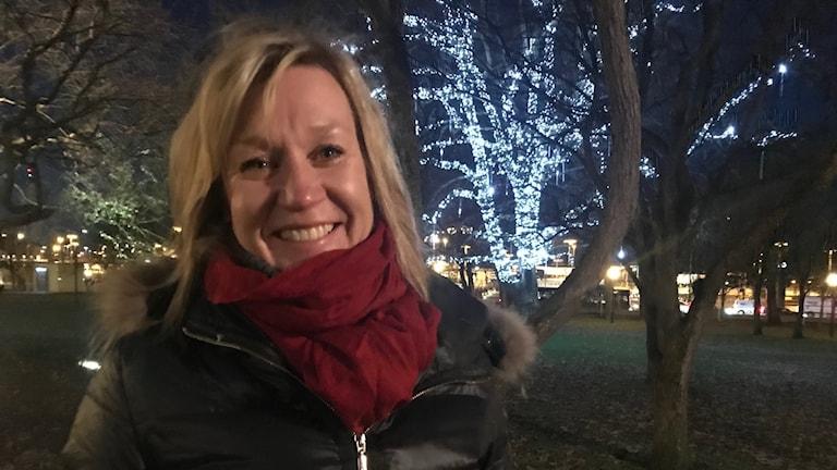 Kvinna med röd sjal, ljust hår framför ljussatt träd i park.