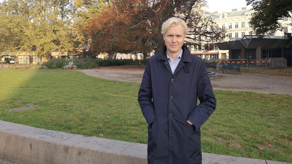 man med blond hår , svart jacka , med träd i bakgrunden