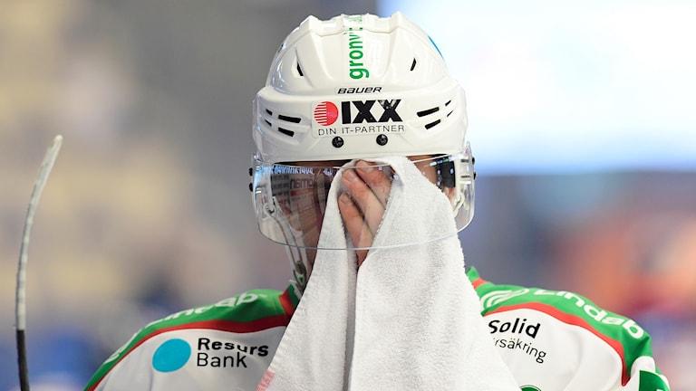 Rögle hockeyspelare torkar ansiktet med en handduk
