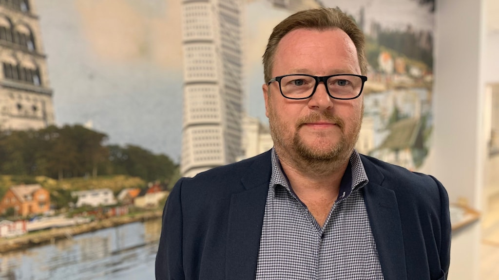 Magnus Nyberg chef för teknikföretagen region Syd står framför en affisch där Turning Torso syns i bakgrunden