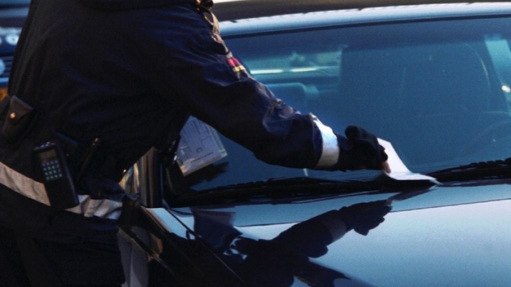 En P-vakt lägger en bot på en felparkerad bil. Foto: Fredrik Persson / Scanpix