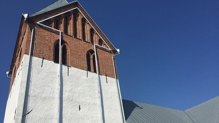 På fasaden till Odarslövs kyrka sitter en jättelik neonpil