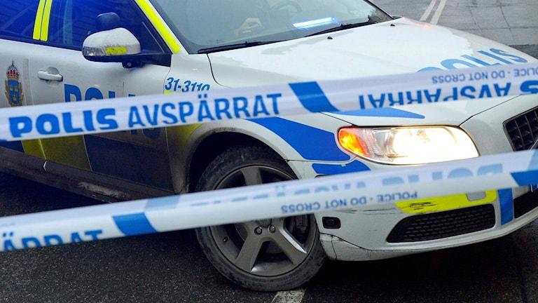 Polisen har spärrat av en gata. På bilden syns en polisbil och polisens avspärrningsband. Foto: Bertil Enevåg Ericson/TT