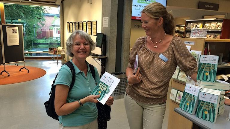 """Agneta Hermansson har just fått boken """"Allt jag kan minnas"""" av bibliotekarien Cecilia Lindgren."""