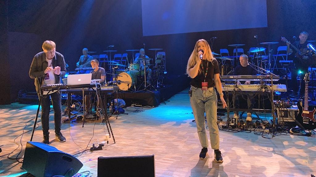 Kvinnlig sångerska och man vid keyboard står på scen med band i bakgrunden.