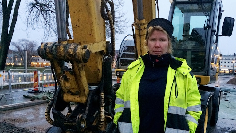 Lina burgman framför grävmaskin