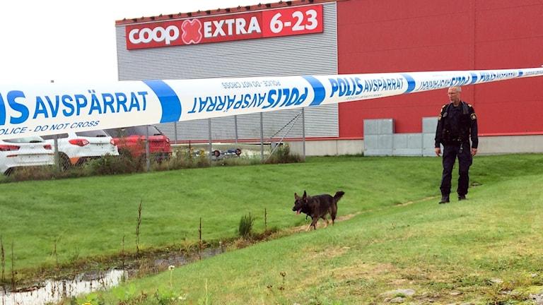 Polis med hund, avspärrningsband, Coop Extra i bakgrunden.