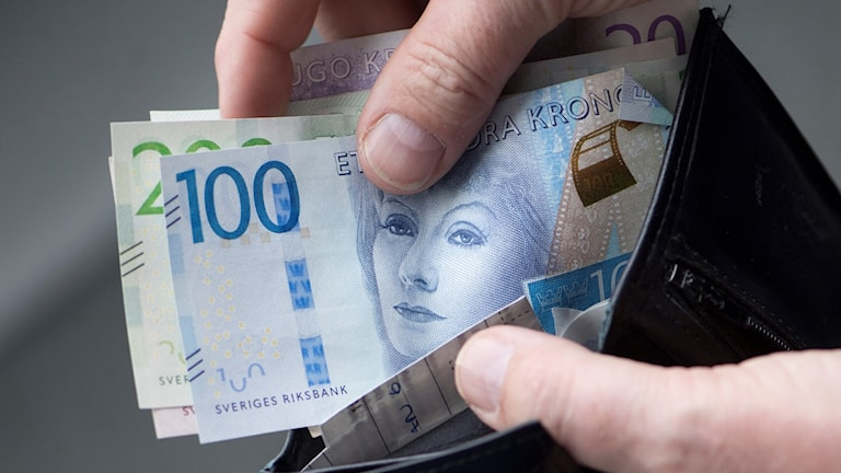 Hand som stoppar ner sedlar i en svart plånbok