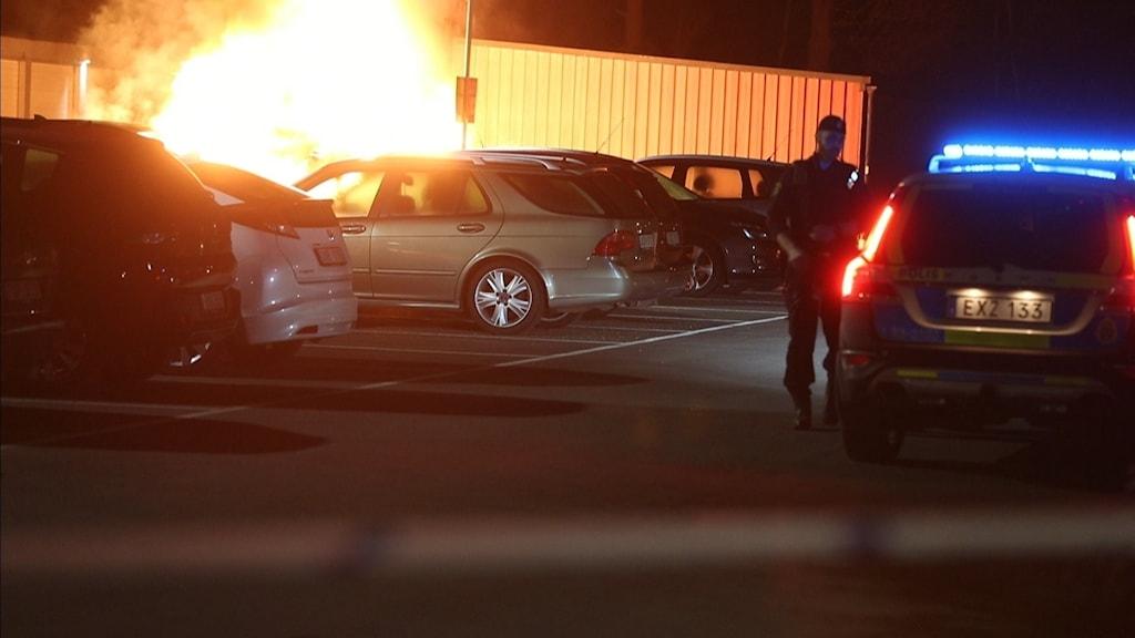 En bil brinner på en parkering och en polis står bredvid vid en polisbil.