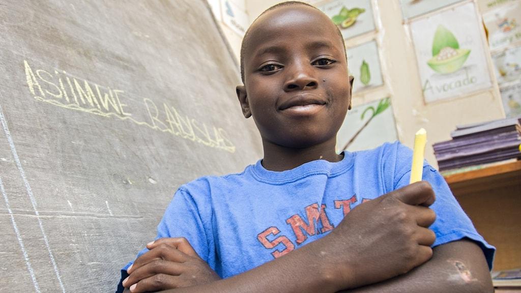 Pojke framför svarta tavlan i ett klassrum. Pojken har en krita i handen