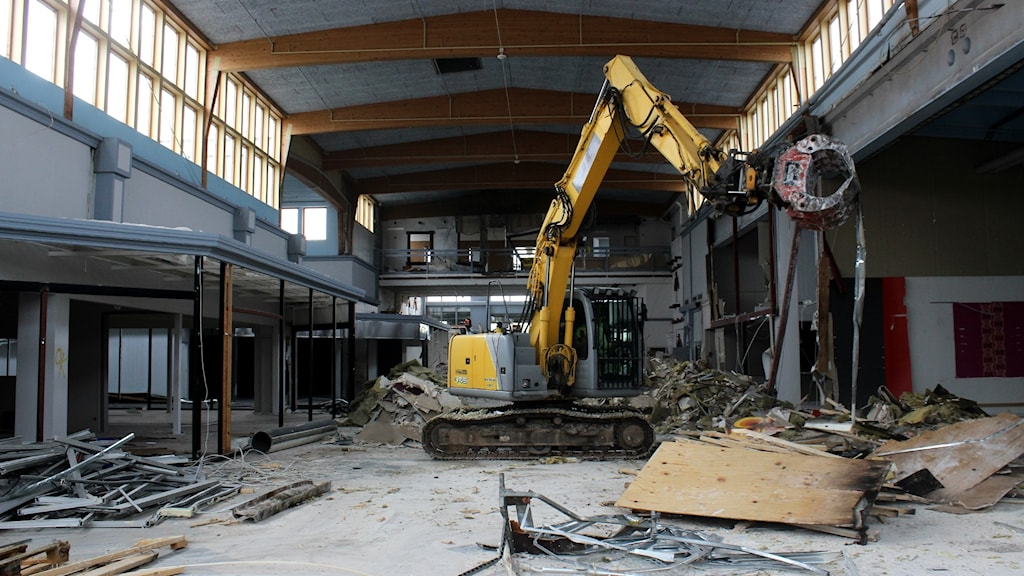 En grävskopa inne i ett fallfärdigt köpcentrum