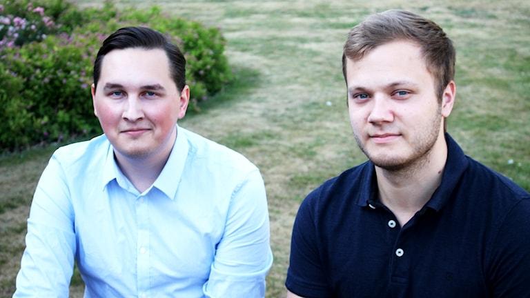 Porträttbild på två yngre män i gräset.