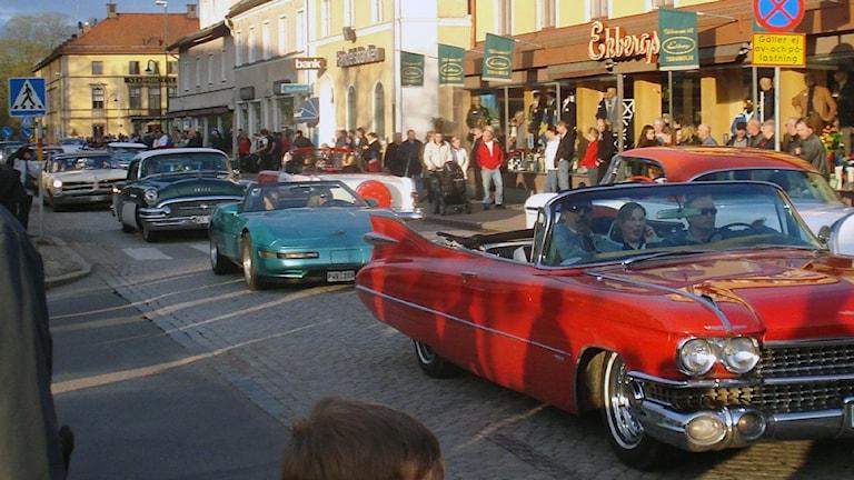 Amerikanska bilar cruisar längs affärsgata
