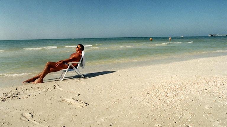 Man i solstol på sandstrand. Foto: Ulf Berglund/Scanpix