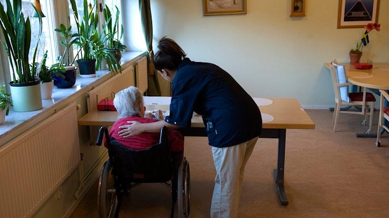 En äldre kvinna i rullstol och en sköterska bredvid som håller en arm på kvinnans rygg.