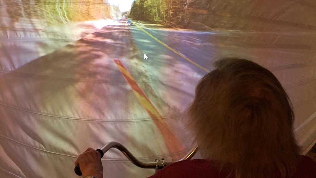 En kvinna med grått hår håller i ett styre framför en skärm med en väg projicerad på sig.