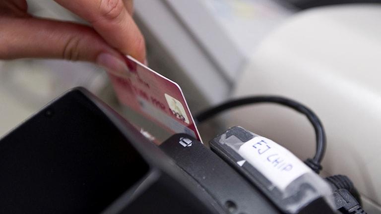 Närbild på en betalning med kontokort i en matbutik.