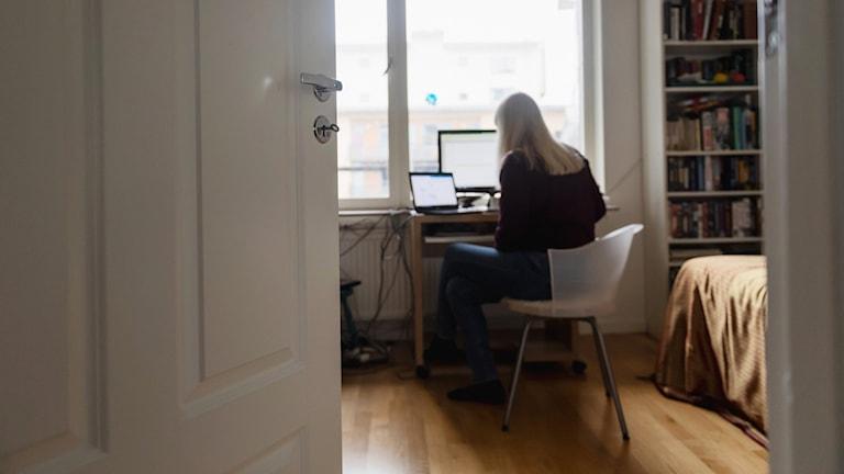 En kvinna jobbar vid en dator på ett skrivbord i sitt sovrum.