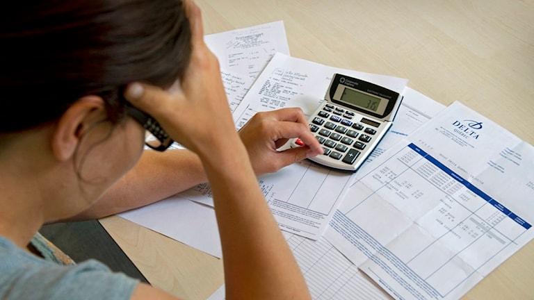 En kvinna sitter med miniräknare och räkningar. Foto: Claudio Bresciani/Scanpix