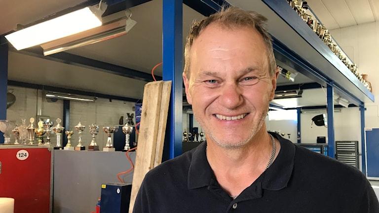Kenneth Hansen i garaget hemma i Götene med pokaler i bakgrunden.