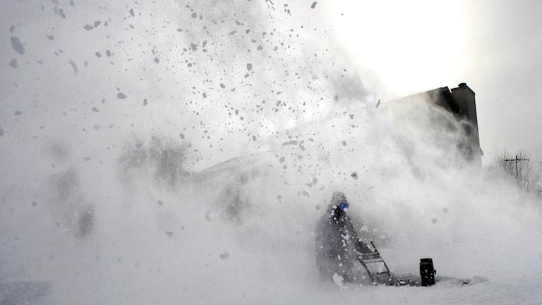 En man jobbar med snöslunga i djup snö. Foto: Scanpix
