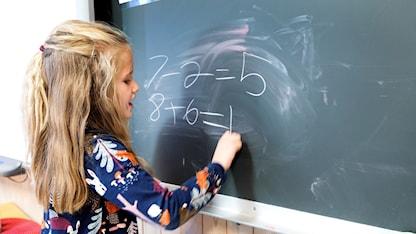 En flicka som räknar på svarta tavlan