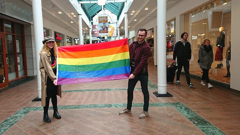 Två personer håller upp en regnbågs-flagga