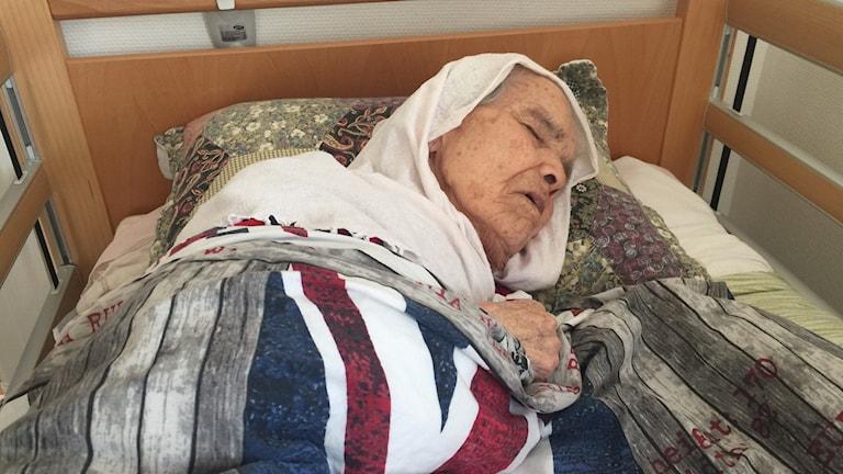 Foto av 106-åriga Bibikhal Uzbek i en säng. Hon har stängda ögon och ser mycket gammal ut.