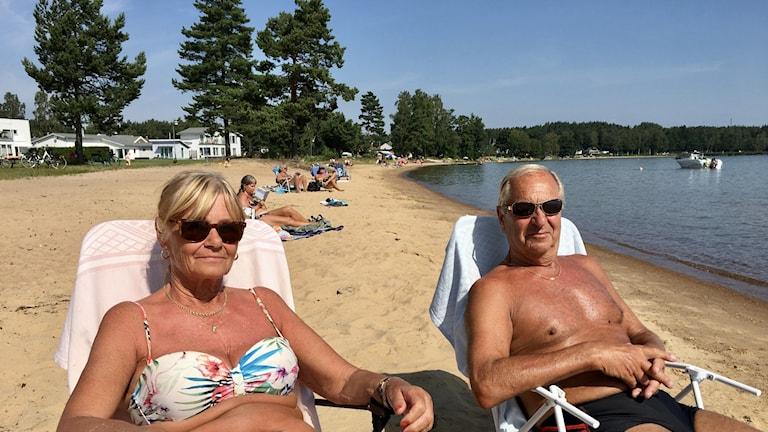 En kvinna och en man sitter i solstolar på stranden