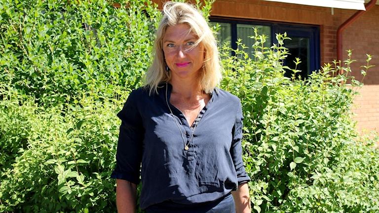 Halvkroppsbild på en blond kvinna framför en buske