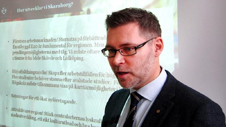 Bjarne Pettersson, regionchef för Västsvenska handelskammaren, visar förslag på hur man kan förbättra Skövde som stad och Skaraborg som region. Foto: Mary Chitgar / P4 Skaraborg Sveriges Radio