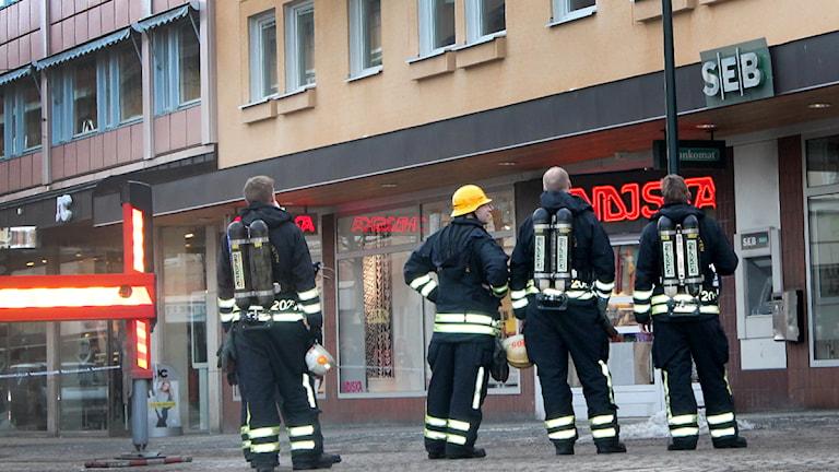 En kvartett brandmän följer släckningsarbetet från gatan. Foto: Erik Grönlund