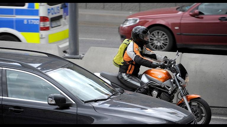 Motorcykelförare på en motorcykel och personbilar. Foto: Janerik Henriksson /TT