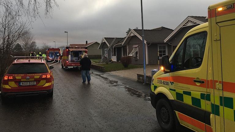 En villabrand med brandbilar och ambulans på plats.