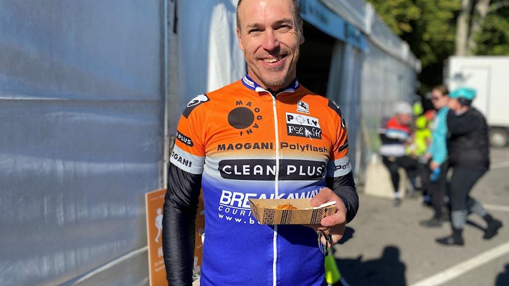 Cyklist med en matportion i handen
