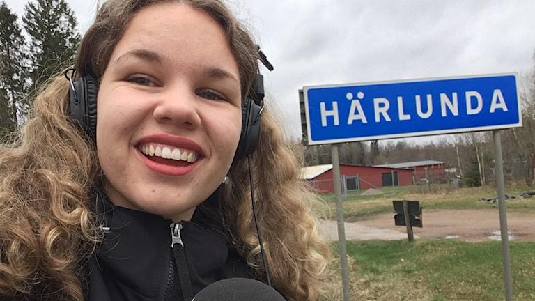 En tjej med lockigt hår står framför skylten till Härlunda.