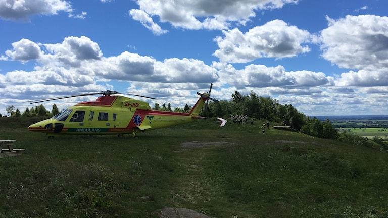 Ambulanshelikopter står på ett fält.