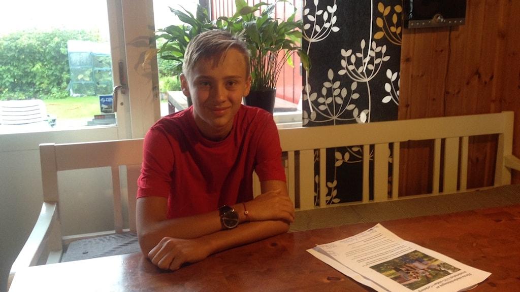 Albin Blomster sitter i en soffa vid ett köksbord.