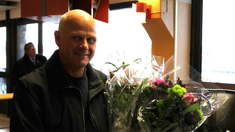 Åke Svanstedt med flera blombuketter i famnen. Foto: Viktoria Svedlund P4 Skaraborg