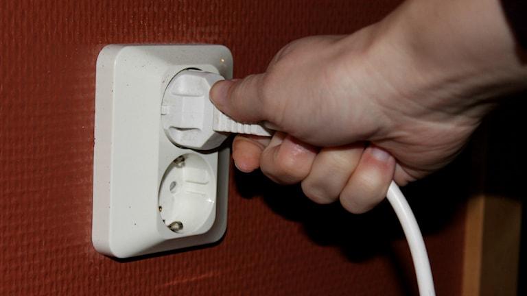 En hand som sätter in in en sladd i ett eluttag. Foto: Viktoria Svedlund/P4 Skaraborg