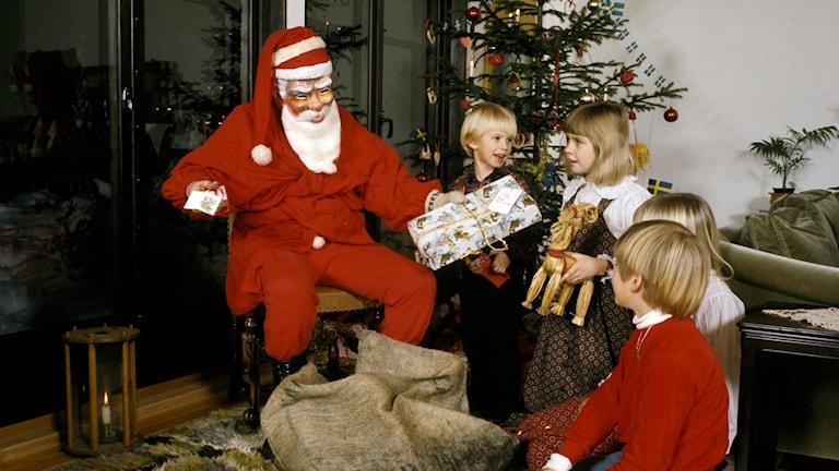 En jultomte delar ut julklappar till barn i hemmet på julafton. Foto: Jan Collsiöö /TT