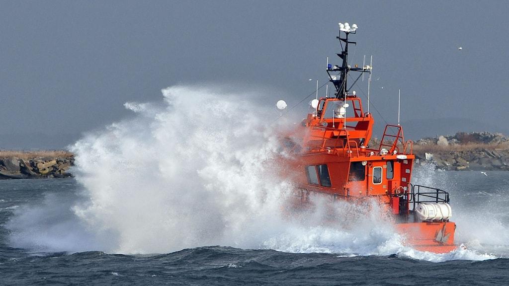 En båt omringas av kraftigt skummande vatten på grund av hårda vindar.