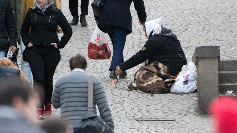 En kvinna sitter på gatan och tigger pengar. Foto: Fredrik Sandberg/ TT