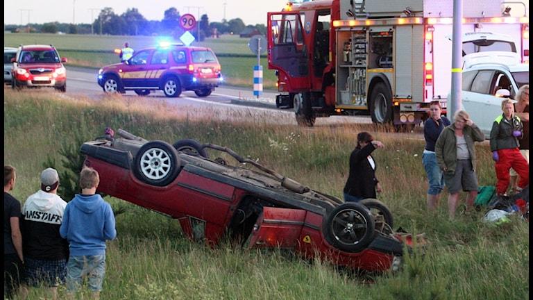 Röd A-traktor ligger på taket intill vägen. Räddningsfordon och några som står och tittar på olycksplatsen. Foto: Torbjörn Axelsson.