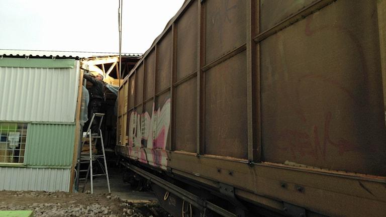 En vagn från ett godståg har kört rakt in i en byggnad med plåtväggar. Foto: Jenny Josefsson / Sveriges Radio.