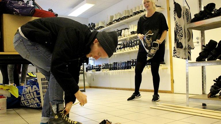 Axel Fernhag provar skridskor. I bakgrunden Julia Hildorzon. Foto: Marie Schnell /Sveriges Radio